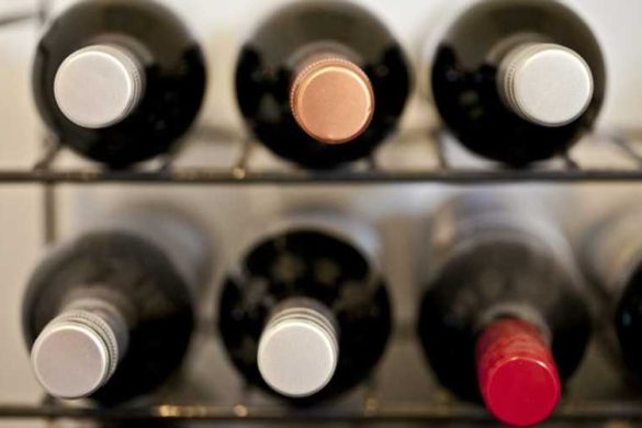 Close-up, front-view of wine bottles stored in a wine rack.